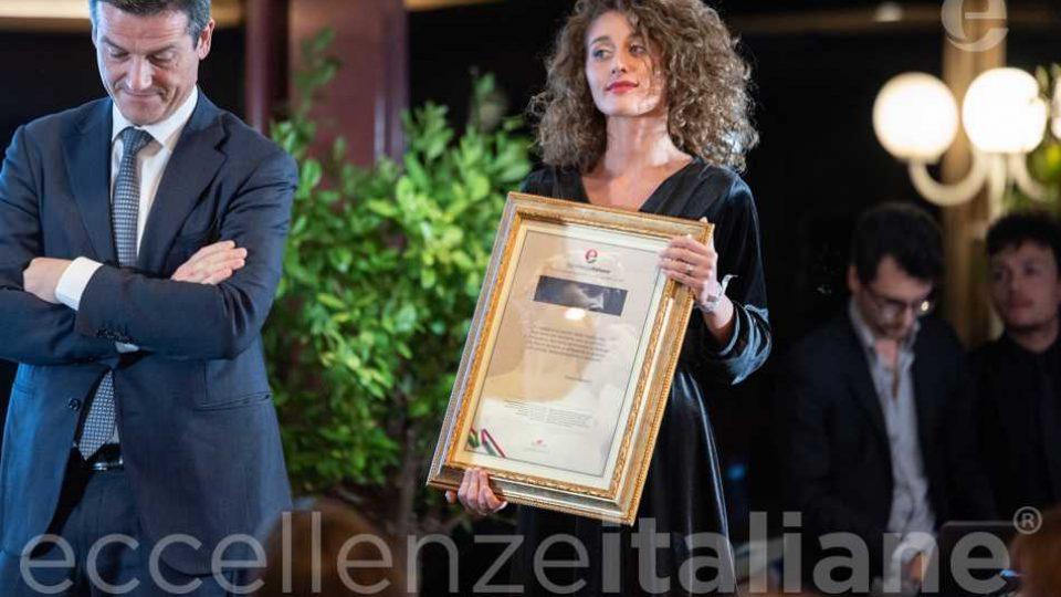 Orazio Iacono - cornice con la motivazione del premio Eccellenze Italiane retta dall' hostess