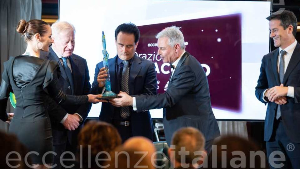 Riccardo Longo consegna il premio Eccellenze Italiane 2019 a Orazio Iacono alla presenza di Sebastiano D'Angelo